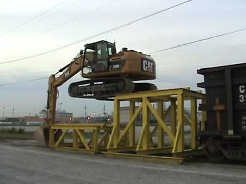 An excavator climbs onto a rail car to unload crushed rock