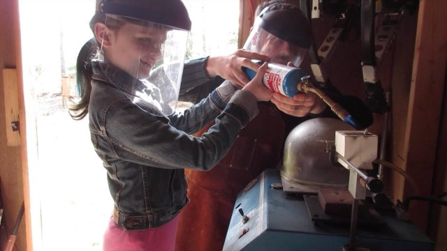 Dad teaches his daughter how to cast a ring from scrap pewter