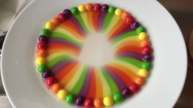Skittles candy dissolves into rainbows