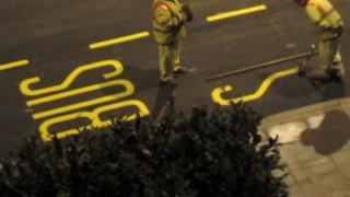 City workers paint letters on a London road