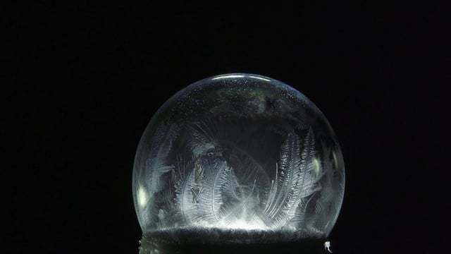 Ice crystals form on the surfaces of backlit bubbles