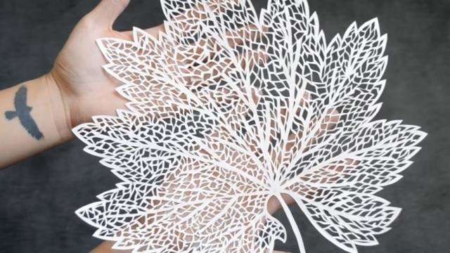 Hand cutting an intricate paper leaf stencil