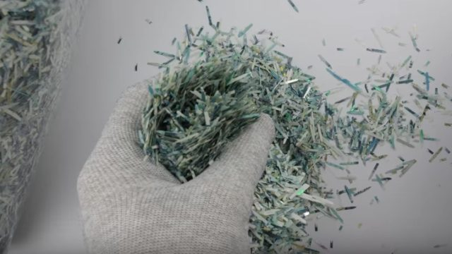 A Bank of England five pound note is reconstructed from shreds, a time lapse