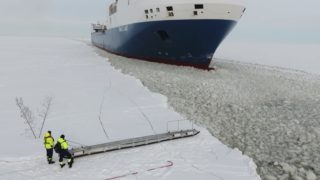 A pilot boards a moving ship in icy Finnish waters