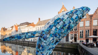 Skyscraper, a giant found-plastic whale breaches in a Bruges canal
