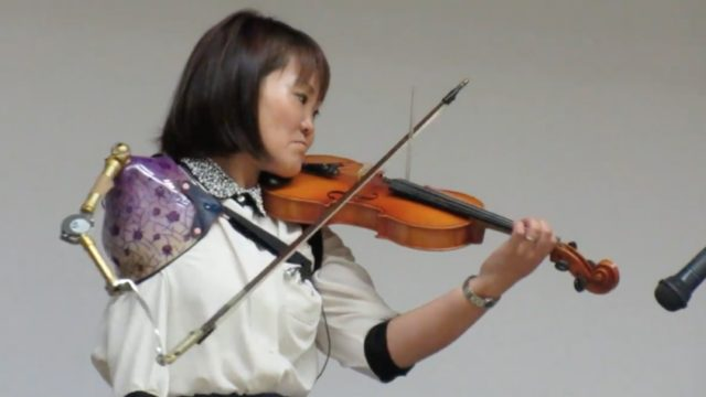 Manami Ito plays violin with her prosthetic arm