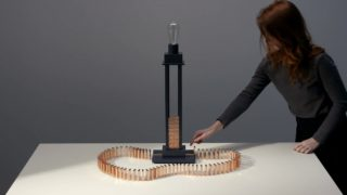 Conductive copper dominoes topple to turn on this lamp