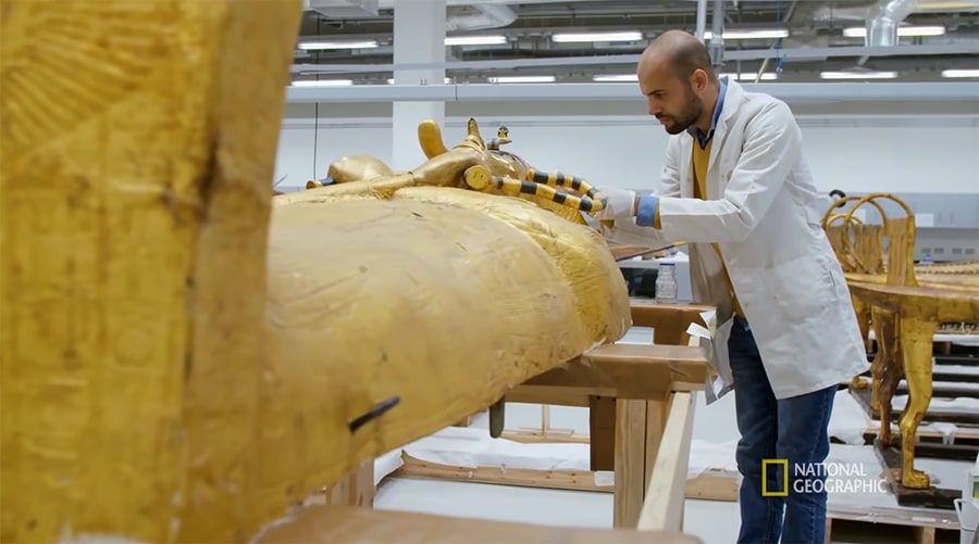 Conservator Ahmed Abdrabou studies the wood and gold-leaf